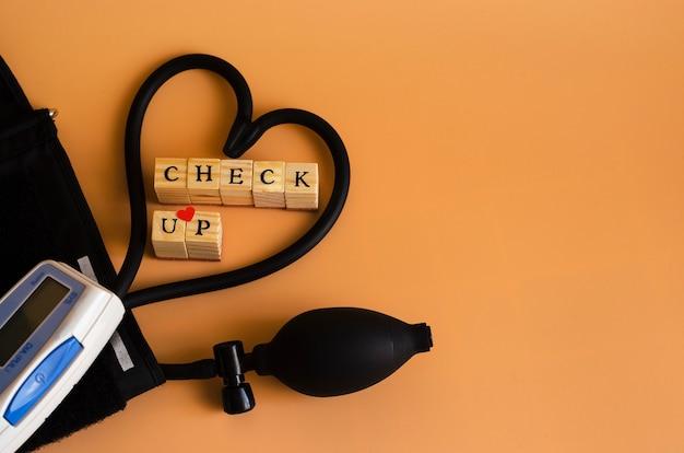 La palabra chesk up y un dispositivo para medir la presión sanguínea en naranja