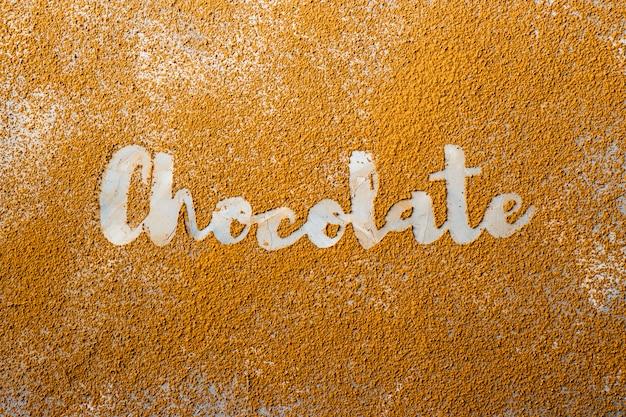 La palabra chocolate está impresa en blanco sobre fondo de cacao en polvo.