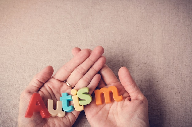 Palabra colorida del autismo en las manos, día del autismo de wolrd, mes de concientización del autismo de abril