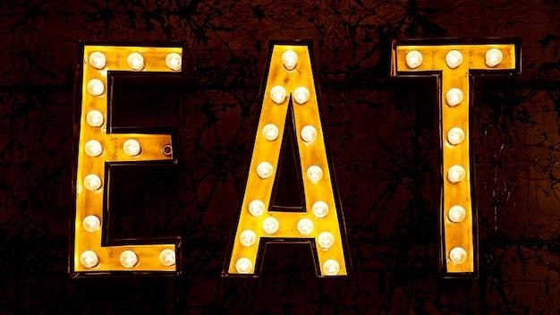 La palabra comer escrita por bombillas. cartel de la calle
