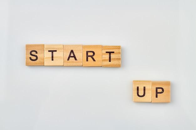 Palabra de concepto formando con cubo sobre fondo blanco. la puesta en marcha es una nueva empresa en el negocio. buena gestión e innovaciones para el éxito en el trabajo.