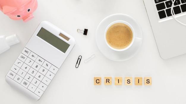 Palabra de crisis hecha con cubos de madera junto a elementos financieros