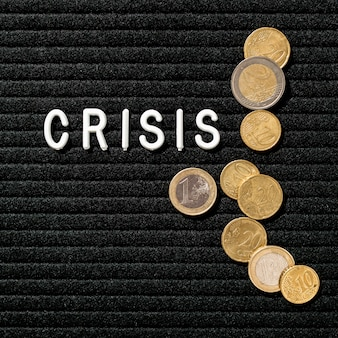 Palabra de crisis y vista superior de monedas