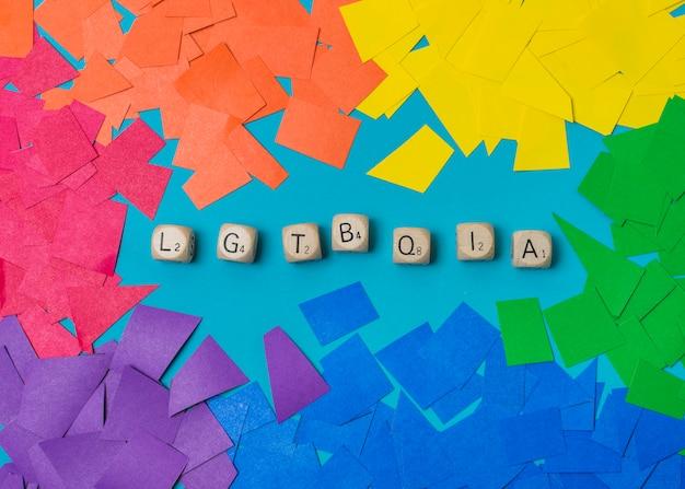 Palabra de cubos lgbtqia y montones de papel en colores alegres.