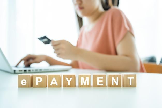 Palabra en cubos de madera compras, irreconocible joven asiática haciendo compras en línea mediante tarjeta de crédito en el pago en línea. niña feliz haciendo una compra online.