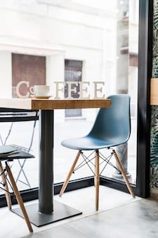 Palabra de café con una taza de café en la mesa de madera