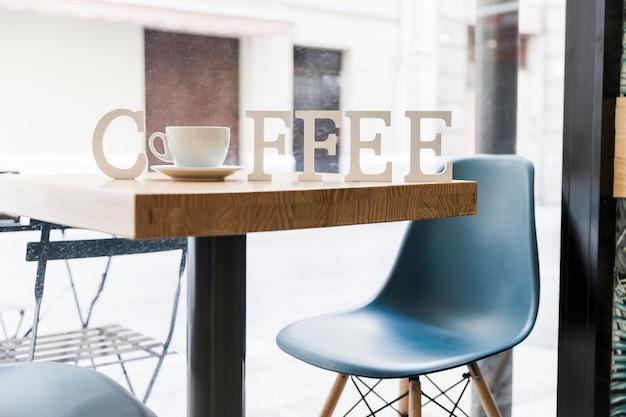 Palabra de café con una taza de café en la mesa en la tienda