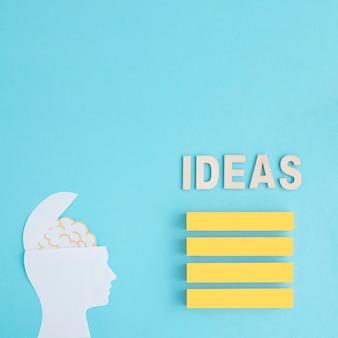 Palabra de ideas sobre la pila de bloques amarillos en blanco con el cerebro en la cabeza de la pluma