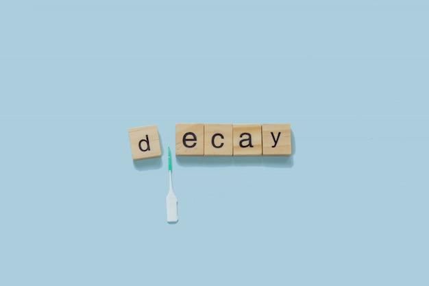 Palabra decadencia deletreada con azulejos de madera sobre un fondo azul.