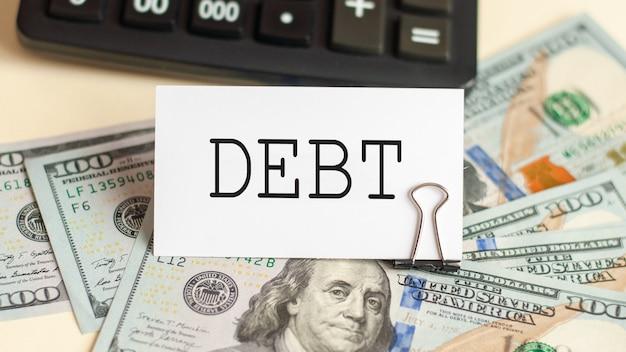 La palabra deuda está escrita en la tarjeta blanca. tarjeta en la pared de billetes de 100 dólares y calculadora
