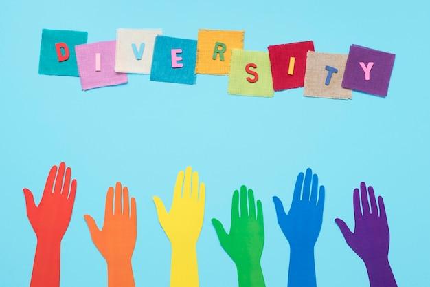 Palabra de diversidad hecha con tarjetas de colores junto a manos de papel de colores