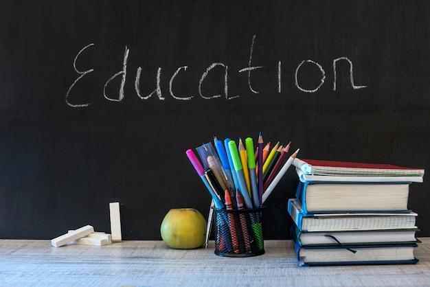 Palabra de educación en la pizarra con libros escolares en el escritorio, concepto de educación.