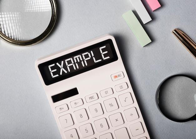 Palabra de ejemplo en calculadora en escritorio de oficina con vista superior de papelería