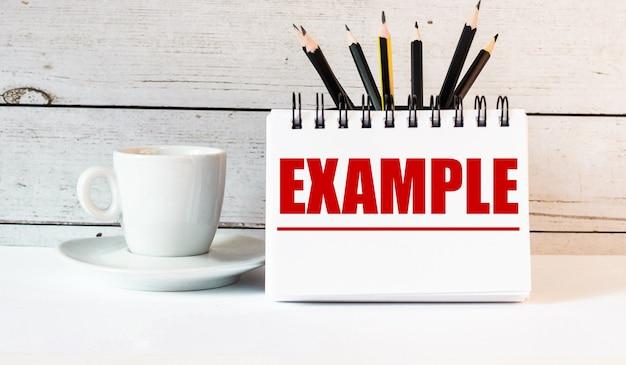 La palabra ejemplo está escrita en un bloc de notas blanco cerca de una taza de café blanca sobre una mesa de luz.