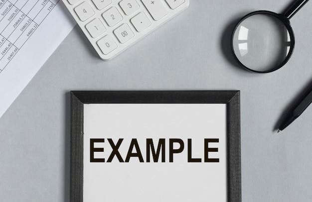 Palabra de ejemplo en el escritorio de oficina con calculadora de papeles y vista superior de vidrio de aumento