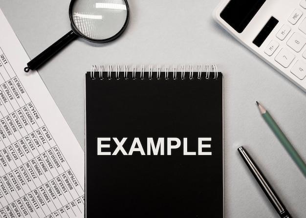 Palabra de ejemplo en la mesa de oficina con calculadora de documentos y lente de aumento plana