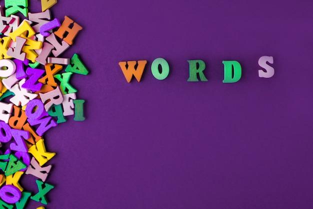 Palabra escrita con letras de bloque de madera junto a un montón de otras letras sobre la composición de la superficie del tablero de madera