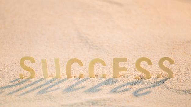 Palabra de éxito con el alfabeto de madera en la playa de arena