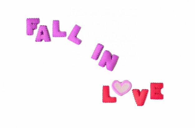 La palabra fall in love deletreada con galletas del alfabeto y malvavisco en forma de corazón