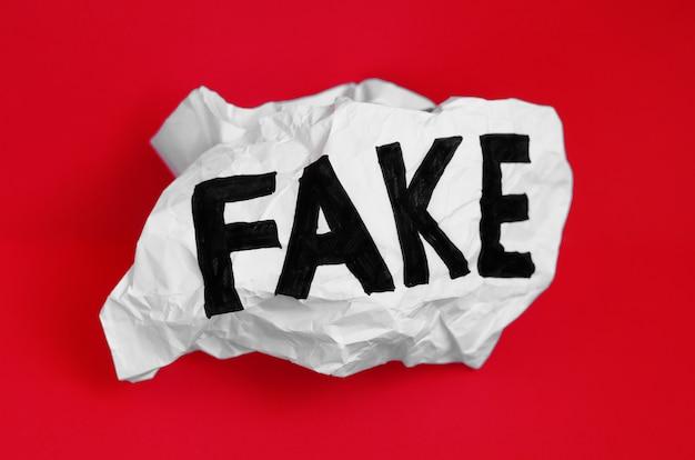 La palabra falsa sobre papel arrugado sobre un fondo rojo.