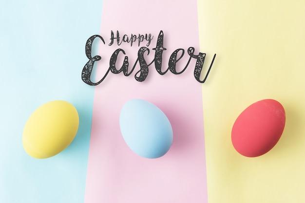 Palabra feliz de pascua con los huevos de pascua en colores pastel