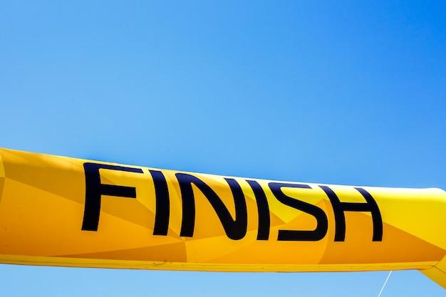 Palabra finalizar en una pancarta amarilla contra un cielo azul.