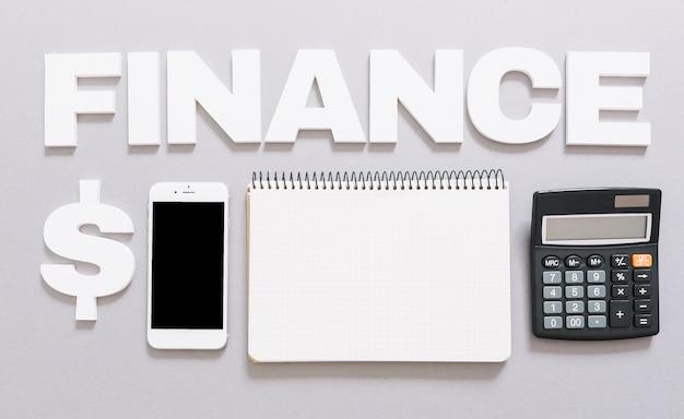 Palabra de finanzas con signo de dólar; teléfono móvil; cuaderno espiral y calculadora sobre fondo gris