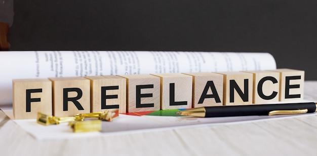 La palabra freelance está escrita en cubos de madera cerca de la pluma y el documento.