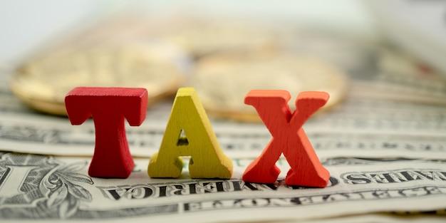 Palabra de impuestos de madera en billetes y monedas de oro. concepto de pago de impuestos, beneficio o cargo financiero obligatorio.