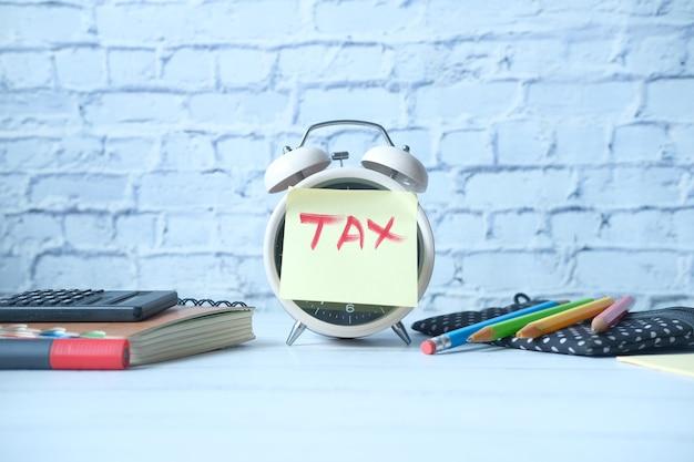 Palabra de impuestos sobre el despertador con estacionaria en la mesa