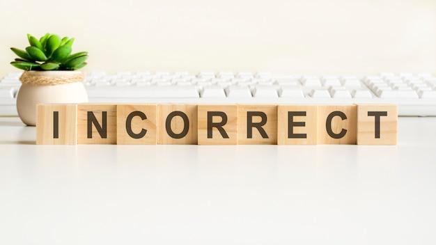 Palabra incorrecta hecha con bloques de madera. conceptos de vista frontal, planta verde en un florero y teclado blanco sobre fondo