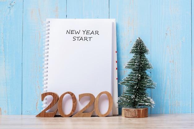 Palabra de inicio de año nuevo 2020 en cuaderno y número de madera.