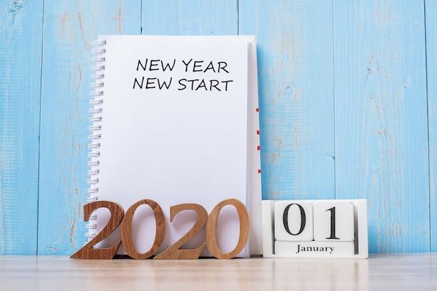 Palabra de inicio de año nuevo 2020 en el cuaderno y número de madera.