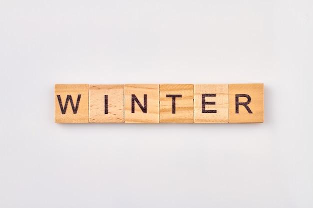 Palabra de invierno sobre bloques de madera. concepto estaciones del año. cubos de madera con letras aisladas sobre fondo blanco.