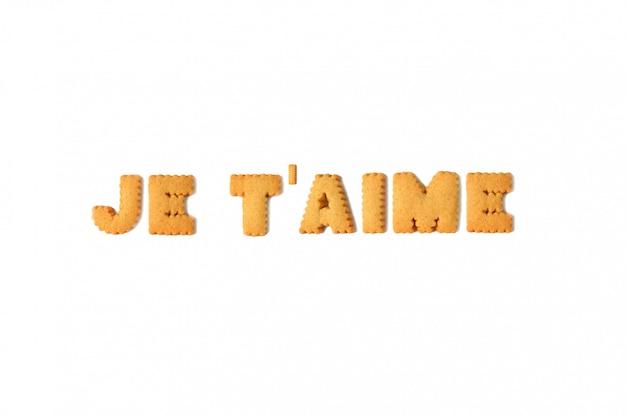 La palabra je t'aime o te amo en francés deletreada con galletas del alfabeto