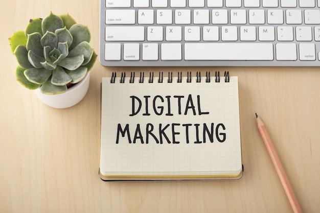 Palabra de marketing digital en un portátil con lápiz y teclado de computadora