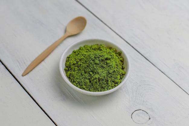 Palabra matcha hecha de té verde matcha en polvo y cuchara de bambú en blanco. copiar
