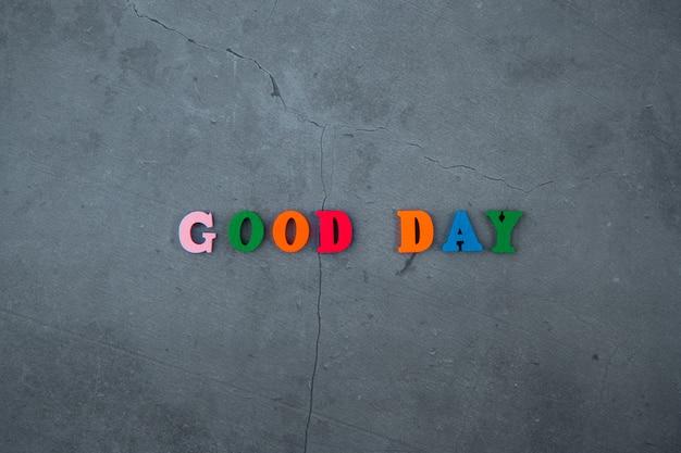 La palabra multicolor de buen día está hecha de letras de madera en una pared enlucida gris.