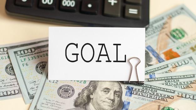 La palabra objetivo está escrita en la tarjeta blanca. tarjeta en la pared de billetes de 100 dólares y una calculadora