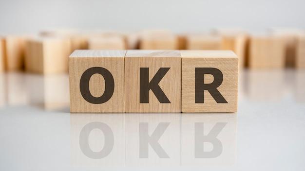 La palabra okr está formada por bloques de construcción de madera sobre la mesa gris, concepto
