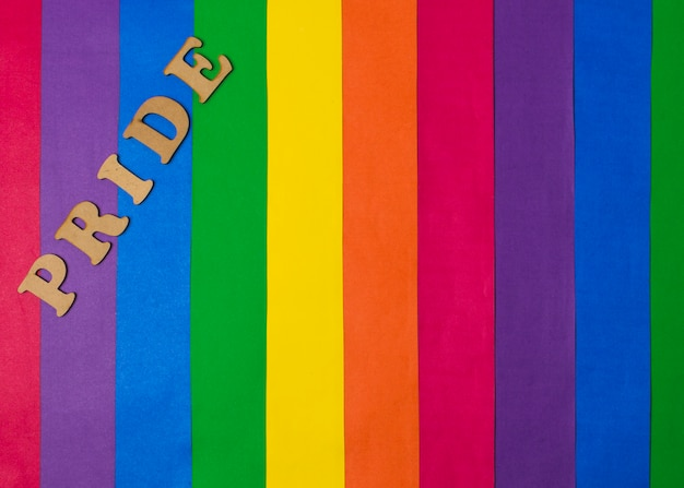 Palabra de orgullo de madera y brillante bandera gay.