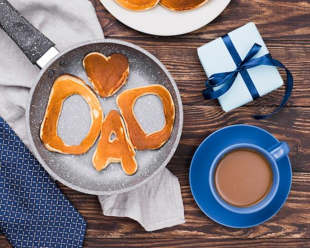 Palabra de papá escrita en bollos de pan y café