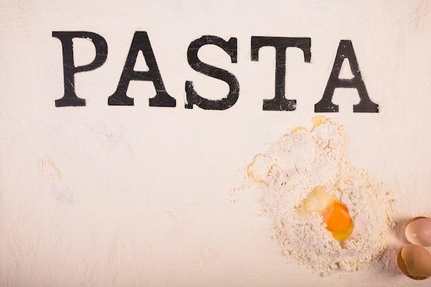 Palabra de pasta color negro sobre harina y huevo