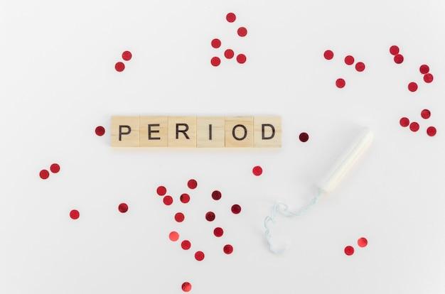 Palabra de período con letras scrabble y lentejuelas rojas