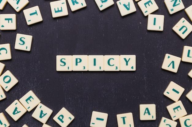 Palabra picante en letras scrabble sobre fondo negro