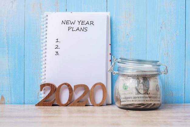 Palabra de planes de año nuevo 2020 en cuaderno, frasco de vidrio de dinero y número de madera.