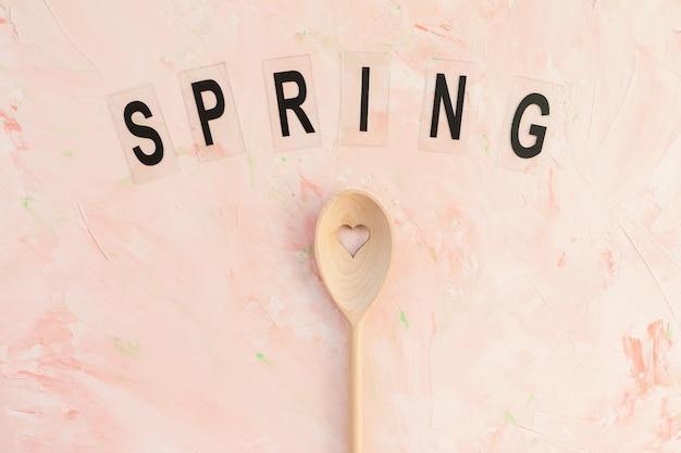 Palabra primavera y cuchara de agitación sobre un fondo rosa