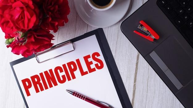 La palabra principios está escrita en rojo en un bloc de notas blanco cerca de una computadora portátil, café, rosas rojas y un bolígrafo.