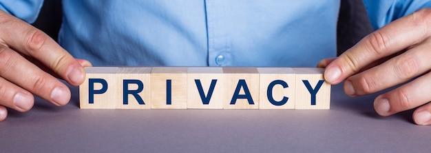 La palabra privacidad está formada por cubos de madera por un hombre