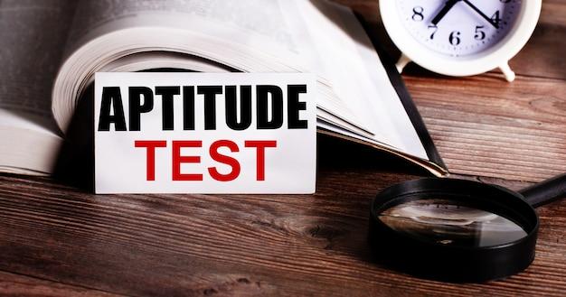 La palabra prueba de aptitud escrita en una tarjeta blanca cerca de un libro abierto